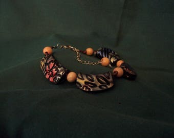 Black polymer clay beads with red, blue and gold accents.