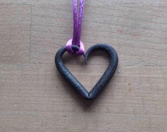 A blacksmith made heart pendant