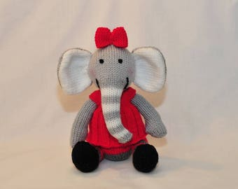 Lottie the Elephant is a cute elephant in a beautiful dress and bow, hand knitted toy elephant, a plush softie animal.