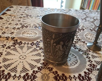 Tin cup with motives and marks