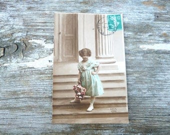 Vintage 1900s recolored French postcard  lovely blue dress girl with a bouquet