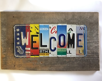 WELCOME upcycled recycled license plate art sign on barn wood tomboyART peace bienvenidos
