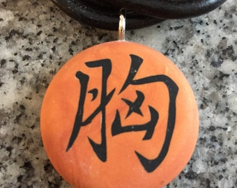 Japanese kanji COURAGE symbol hand carved on a polymer clay burnt orange color background. Pendant comes with a FREE necklace