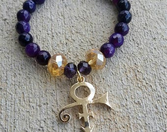 Gold PRINCE symbol charm bracelet with purple faceted agate and acrylic accents.