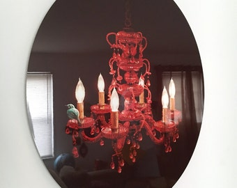 "Crimson Perch--Illustration of a teal bird perched upon a red crystal chandelier Infused onto a 20"" High Gloss Metal Oval"