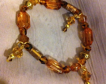 Topaz and gold stretch beaded bracelet with Celtic knot beads.