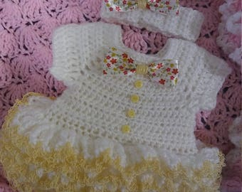 "White crochet ""onsie"" with yellow trim, this one is adorable."