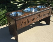 3 bowl dog feeder great for two friendly dogs / two 2 quart bowls for food, 5 quart bowl  for water. 2 paws design in photos.Thanks