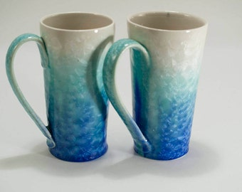 Crystalline glaze white-green-to blue on porcelain mugs