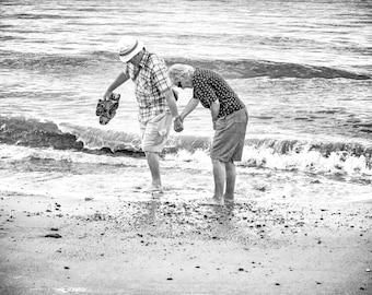 Black & White street photography print, Tourist photo, older couple paddling sea, sandals in hand support, Norfolk England, coastal seaside