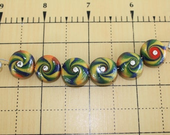 Six yellow, red, blue and green swirl polymer clay beads each with a Swarovski crystal - about 1/2 inch diameter each