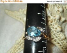 ON SALE NOW on sale Blue Topaz ring,Blue stone,Gold band,18Kt  hge 1980s  size 9-9.5   cz are  3 leaf shape surrounding ring Excellent Condi