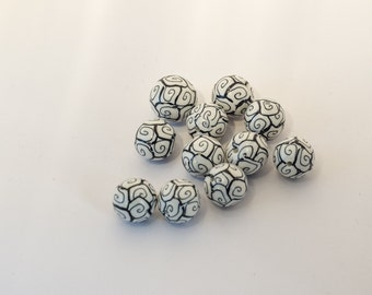 set of handmade polymer clay beads and white spiral pattern