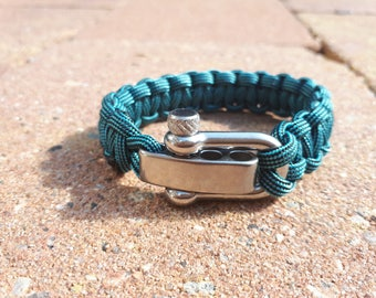 Survival bracelet / paracord black blue striped from extra thick quality cord with a stainless steel shackle closure.