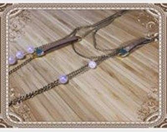 Long necklace with gold chain,brown pieces of leather and pearl beads
