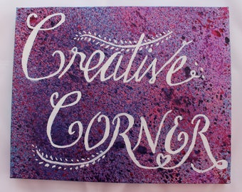 Creative Corner Canvas for your creative space.  White hand lettering on a Pink, Purple and blue splattered background.