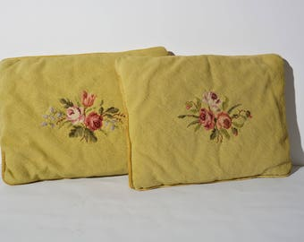 Two vintage needlepoint cushions gold colored with roses.