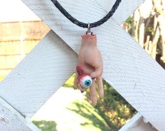 Hand Holding an Eye Pendant