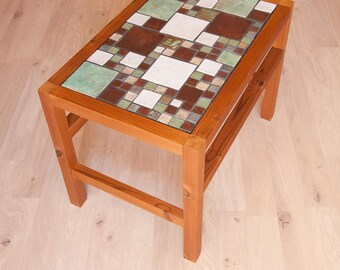 Low coffee table with a top composed of various materials.