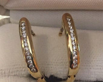 14kt yellow gold half hoop earrings with approx 0.24ct round cut diamonds..