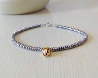 minimalist bracelet, rings of hematite, gold pendant, silver bracelet