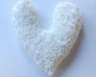 Soft white furry comfort pillow, shaped like a heart with rose swirl texture in fur.