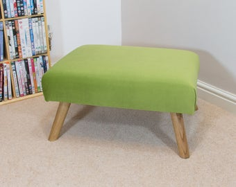 Footstool with green velvet and oak legs
