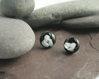 Black glass stud earrings with a white glass design.