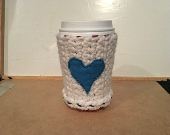 White crotcheted coffee cozie with blue heart