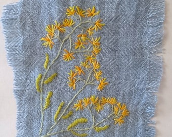 yellow mimosa embroidered on bluish linen patch