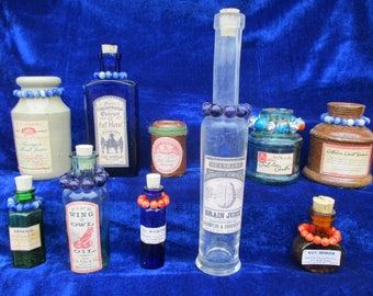 a group of very old bottles with magic wiccan potion labels and beads
