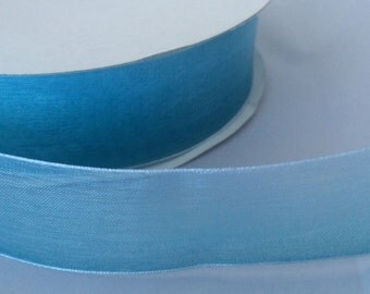 Sheer two tone - Teal blue graduating to white. Woven edge. 1 inch wide.
