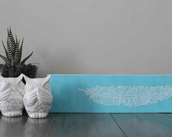 Blue hand painted feather sign