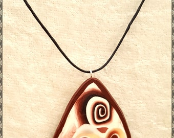 Shell inspired Triangular Pendant Approx 4cm each side, it has an ajustable 1cm cotton cord necklace.
