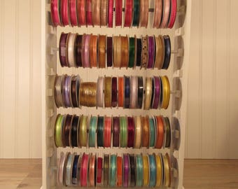 Very nice white wood ribbon holder/organizer which comes with 74 full or partially full spools of ribbons of various colors