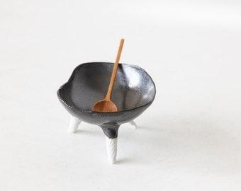 Dark metallic hand built bowl with white tripod feet in porcelain and teak spoon
