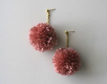 Pom-pom drop earrings dangling on gold chain and gold stud in soft dusty pink