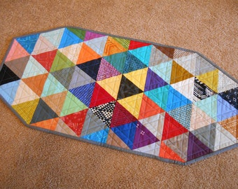 Modern bright quilted table runner with triangles in primary colors