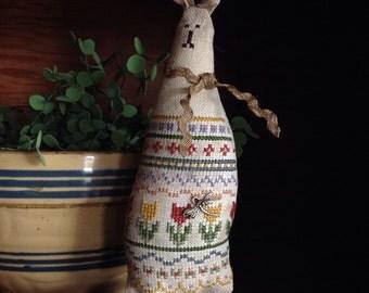 Primitive cross stitched sampler bunny on a door knob