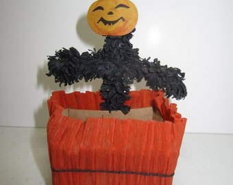 1920's Halloween crepe paper nut cup in orange with black fringed crepe paper scarecrow body with die cut jack o lantern face