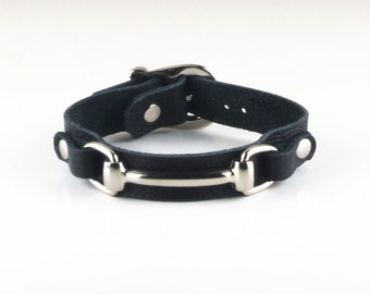 Leather wristband with horse snaffle bit and buckle.