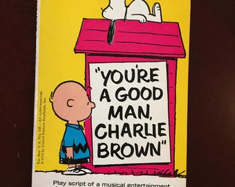 "Autographed paperback script of ""You're A Good Man, Charlie Brown""."