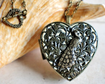 Peacock music box locket, heart shaped  locket with music box inside, in bronze with peacock on cover.