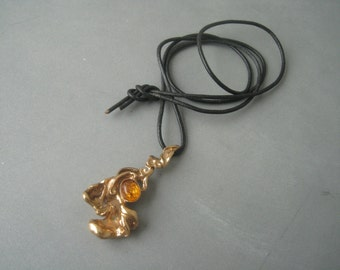 Modernist gilt bronze pendant with a leather cord, Finland.