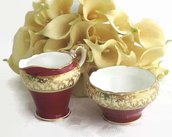 Aynsley sugar bowl and creamer, England, burgundy and cream bands, gilt edges and gilt pattern of leaves, 1930s / 40s