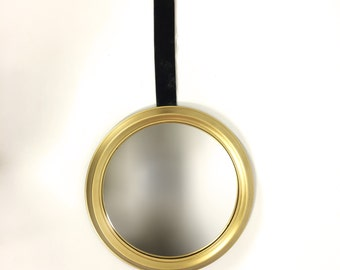 Round convex mirror with a golden frame.