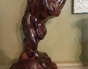 Big Ceramic Sculpture of couple embracing in a kiss on boulder dark brown