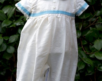 Ivory silk dupion romper suit with blue detail,bonnet and shoes.