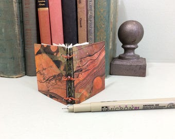 Tiny coptic journal with recycled pages, beads, two pockets, and vintage dictionary page end papers. Fun mini journal, gift book.