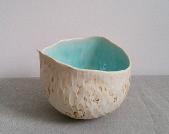 Round organic pinch pot bowl with aqua in glazed interior.